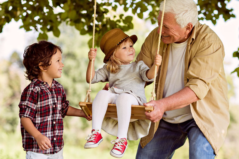 Elderly man pushing a child on a tree swing