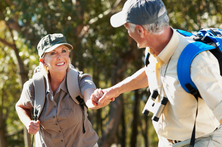 Elderly couple holding hands while hiking