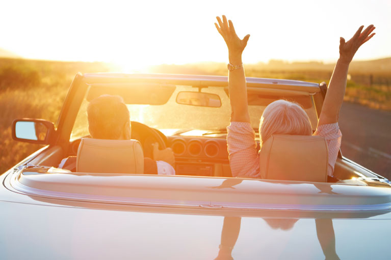 Elderly couple riding down a highway in a convertible